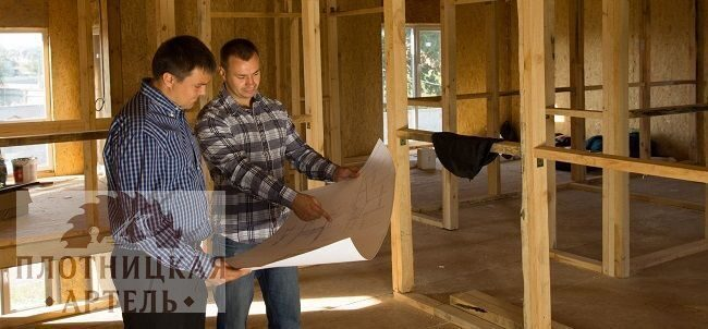 Two builders discussing the interior of a house
